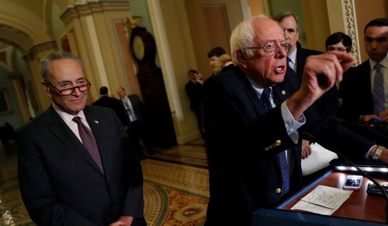 Sen. Bernie Sanders (I-VT), accompanied by Senate Minoirity Leader Chuck Schumer, speaks with reporters following the party luncheons on Capitol Hill in Washington